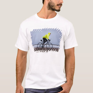 Man bicycles on a cold and foggy winter day. T-Shirt