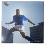 Man bouncing soccer ball on his head ceramic tiles
