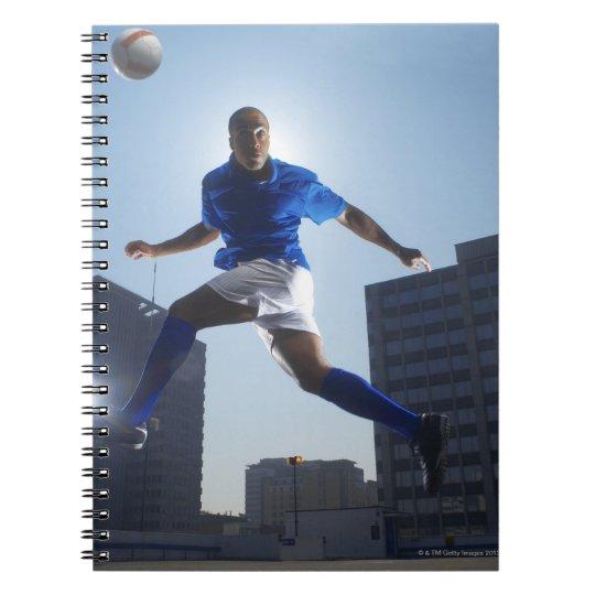Man bouncing soccer ball on his head spiral notebook