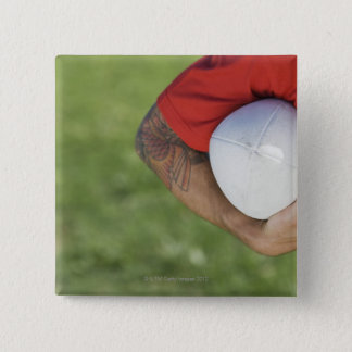 Man carrying rugby ball pinback button