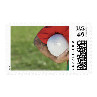 Man carrying rugby ball stamps