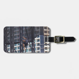 Man climbing up a steel ladder tags for bags