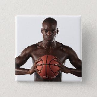 Man clutching basketball pinback button