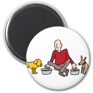 Man feeding his two dogs 2 inch round magnet