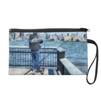 Man Fishing Off Hoboken Pier Wristlet Clutch