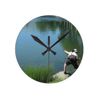 Man fly fishing on a mountain lake round clock