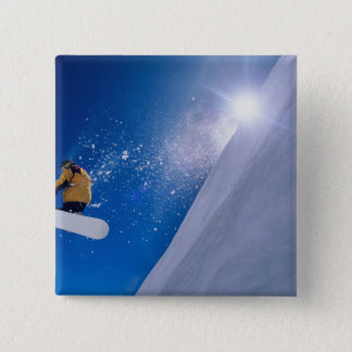 Man flying through the air on a snowboard with button