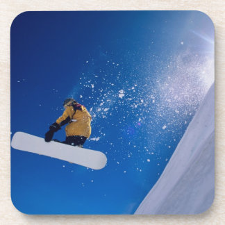 Man flying through the air on a snowboard with beverage coasters