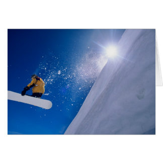 Man flying through the air on a snowboard with greeting card