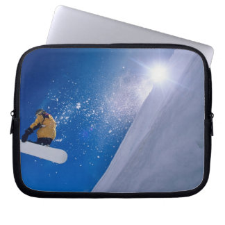 Man flying through the air on a snowboard with laptop sleeves