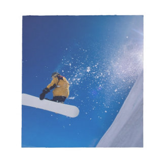 Man flying through the air on a snowboard with memo notepad