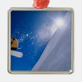Man flying through the air on a snowboard with christmas tree ornaments