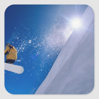 Man flying through the air on a snowboard with square sticker