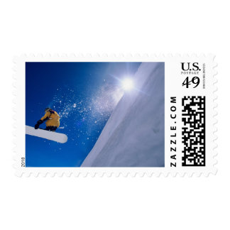 Man flying through the air on a snowboard with stamp