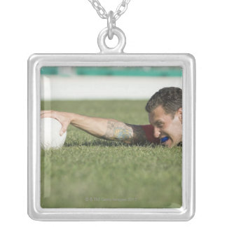 Man grabbing rugby ball silver plated necklace
