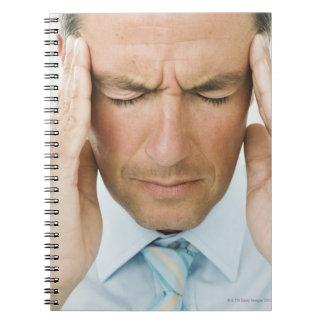 Man hands on head spiral notebook