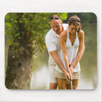 Man helping woman golf mouse pad