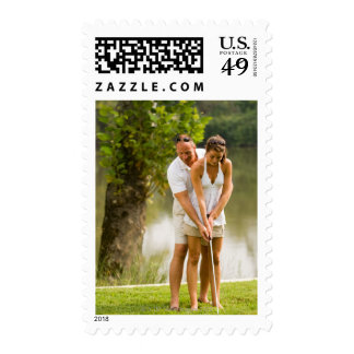 Man helping woman golf postage