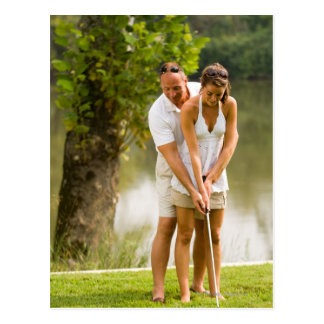 Man helping woman golf postcard