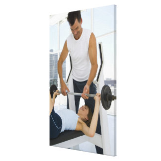 Man helping woman with weightlifting canvas print