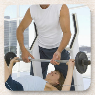 Man helping woman with weightlifting drink coaster