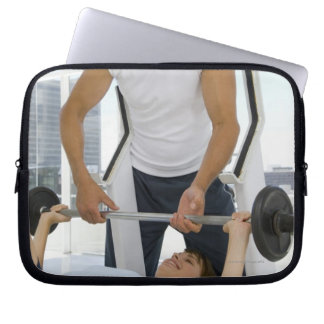 Man helping woman with weightlifting laptop sleeves