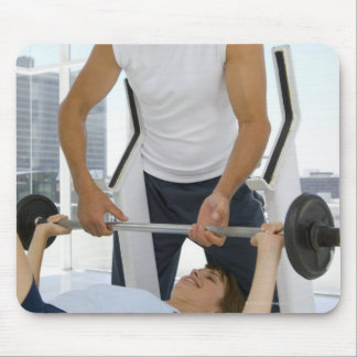 Man helping woman with weightlifting mouse pad