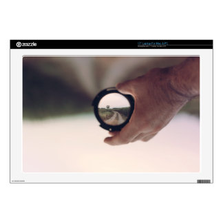 Man holding a lens that shows inverted image laptop skin