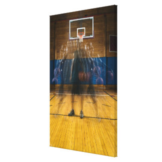 Man holding basketball standing on court, stretched canvas print