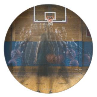 Man holding basketball standing on court, dinner plate