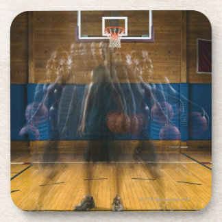 Man holding basketball standing on court, drink coaster