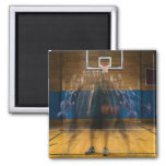 Man holding basketball standing on court, 2 inch square magnet