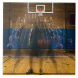 Man holding basketball standing on court, large square tile