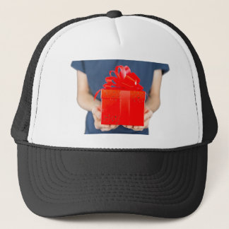 Man holding red christmas gift in front of body trucker hat