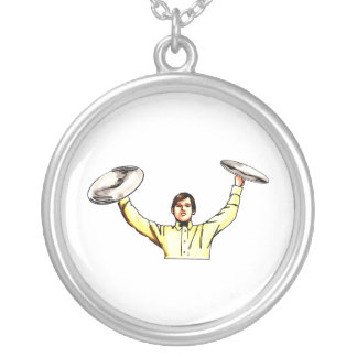 Man holding up cymbals yellow shirt round pendant necklace