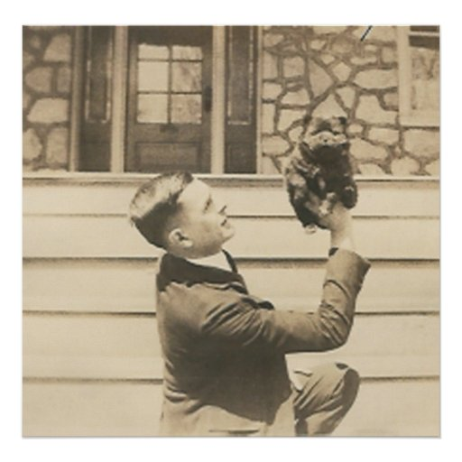 man holding up small animal  with one hand poster