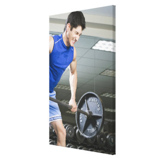 Man in gym, lifting large barbell, clenching gallery wrapped canvas