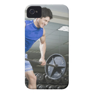 Man in gym, lifting large barbell, clenching iPhone 4 cover