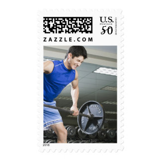 Man in gym, lifting large barbell, clenching postage