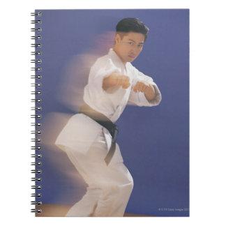 Man in karate stance notebook