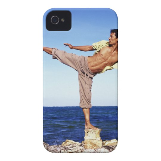 Man in martial arts kicking position, on beach, iPhone 4 case
