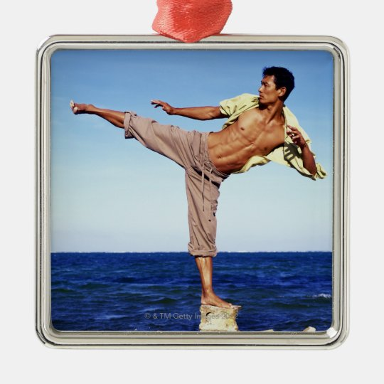 Man in martial arts kicking position, on beach, metal ornament
