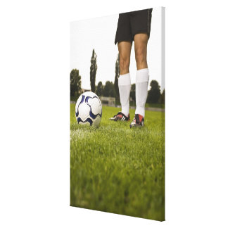 Man in soccer uniform standing with soccer ball canvas print