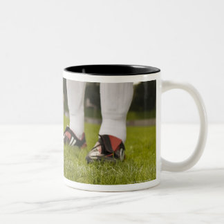 Man in soccer uniform standing with soccer ball Two-Tone coffee mug