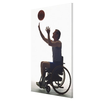 Man in wheelchair playing with basketball canvas print