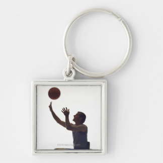 Man in wheelchair playing with basketball keychain