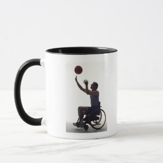 Man in wheelchair playing with basketball mug