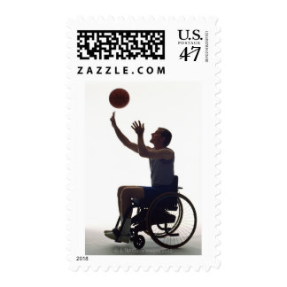 Man in wheelchair playing with basketball postage stamp
