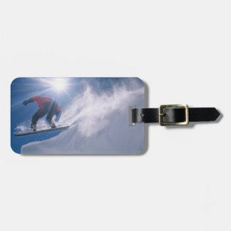 Man jumping off a large cornince on a snowboard bag tag