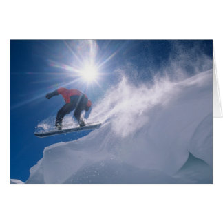 Man jumping off a large cornince on a snowboard card